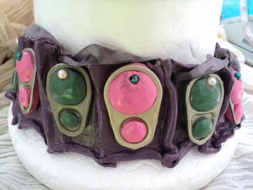 Collier tour de cou en p�te fimo violine d�cor� d'anneaux d�capsuleurs en m�tal argent� avec de la p�te fimo rose et vert incrust�e Le collier se ferme avec un ruban