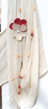 collier sautoir sur fil câblé en métal argenté sur lequel sont enfilées des perles en plastique et porcelaine.Deux fleurs en tissus sont accrochées sur le côté gauche du collier