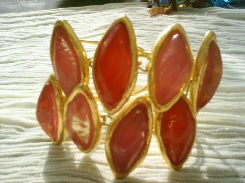 ZIG-ZAG; bracelet sur fil d'aluminium dor� ajustable au poignet, compos� de 8 grosses perles rouge orang� et rose cercl�es de dor�. Largeur 8 cm. Il fait parti des bijoux refaits � neuf avec un vieux collier tr�s imposant,trop lourd et d�mod�. Avec tous les cabochons j'ai pu refaire un collier (vendu) une bague