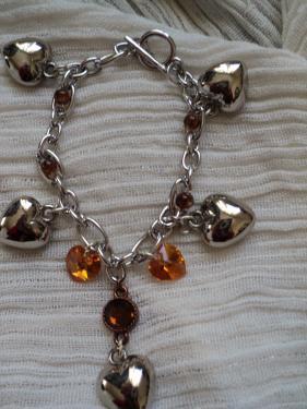 Gourmette en métal argenté  décorée de coeur en métal et deux coeurs en cristal de swaroski ambre et des petites perles rondes ambre