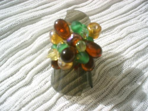 BONBONNIERE bague sur plateau anneau argenté réglable surmonté d'un cabochon irisé entouré de facettes de cristal de swaroski bleu clair et perles de rocaille jaune.     Taille de la bague 2 cms.