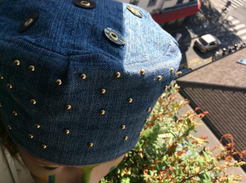 Superbe toque tout en jean délavé et recyclé. Très agréable à porter en toutes saisons. Une constellation de clous à griffes dorés pour signifier la voie lactée.  des confettis de cuir sur le top. Modèle unique.jolie doublure en tissus vert et rose.  Tour de tête : 55 cm