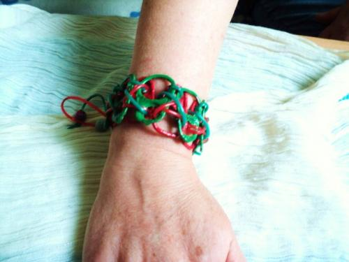 Eh oui vous ne rêvez pas, ce bracelet est fabriqué avec des languettes d'ouverture de boîtes de conserve et beaucoup d'imagination. Les languettes sont peintes avec de la peinture acrylique rouge ou verte et vernies. Les languettes sont disposées tête-bêche et reliées entre elles avec deux fils plastique vert et rouge terminés par deux perles rondes vertes et rouges. Le bracelet s'adapte à toutes les tailles de poignet grâce à un système de boutons qui bloque les fils à la dimension  choisie.