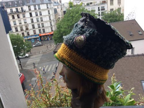 Voici un bonnet toque du plus bel effet qui ira avec bon nombre de vos tenues.tricoté en grosses mailles d'acrylique et de la laine plus fine racordée au top par des ?illets . Le top est composé d'un patchwork de tissus texturé du plus beau rendu. Modèle forcément unique. Tour de tête 68