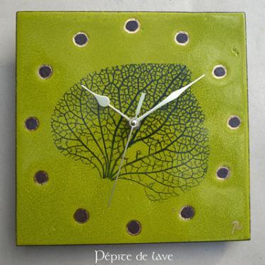 Horloge en lave émaillée Verte nervure de feuille  Cette horloge Verte nervure de feuille en lave émaillée et touches d'or est une création unique. Dim : 25X25 cm Mécanisme silencieux. Fixation au dos