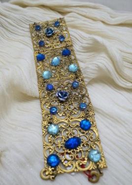 VERSAILLES;Bracelet composé de quatre estampes dorées, décorées avec des fleurs en métal bleu, des perles plates en verre bleu et des cabochons ronds ou ovales bleus. Le bracelet se ferme avec deux clips