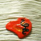 MON COEUR:Tour de cou sur torque argenté, pendentif en pâte fimo rouge vernie, décor paillettes dorées et fin lacet de pâte fimo noire.