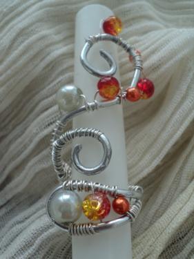 HELENE:en fil d'aluminium argent�, entortill� de fil de cuivre argent� et agr�ment� de perles de cultures gris clair et orange plus petites et de perles de verre orange flamboyant. La particularit� de cette bague est de pouvoir se mettre comme vous le souhaitez, soit longue sur le doigt, ou longue sur la main. Elle peut aussi se r�tr�cir gr�ce au fil d'aluminium qui a la propri�t� de se plier comme on veut. La taille la plus longue est de 6 cm et elle peut r�tr�cir de moiti�.