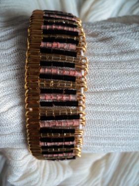 Bracelet original:Bracelet est compos� d'�pingles de s�ret� dor�es, sur lesquelles sont enfil�es des rocailles noires,rose,et dor�es et qui sont dispos�es en alternance.Les �pingles sont parcourues par un �lastique en haut et en bas, le bracelet se r�gle donc sur toutes les tailles de poignet. Le bracelet est plus resserr� sur le poignet et plus large sur le bras,c�t� ouverture de l'�pingle. Le bracelet est � la fois tr�s original et tr�s �l�gant. Vous ferez un