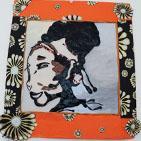 Mama: tableau sur carton recouvert de papier orange, visage dessiné avec de la pâte fimo, et perles,le pourtour est décoré cartonné fleuri.