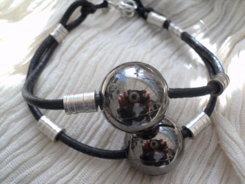 Bracelet en cuir noir et perles en métal argenté,se ferme par un fermoir mousqueton