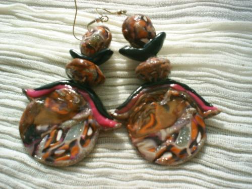 TOKYO:Boucles-d'oreilles en pâte fimo.Pâte fimo milleflori dans les teintes marron caramel, orange, argenté et blanc formant une cercle couvert par moitié de 2 bandes de pâte rose et noir. Le tout est surmonté de 2 perles du même millefiori que le cercle et une perle en pâte fimo noire demi-lune. Longueur 7cm sans l'attache. Boucles-d'oreille pour oreilles percées. Vous serez attiré par le côté japonisant et unique de ces boucles-d'oreille
