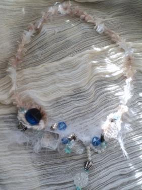 Collier mi-long composé d'un torque en métal argenté,gainé de fil de nylon tissé,et recouvert de laine de soie. Perles de verres blanches et bleues de toutes formes et de toutes tailles, facettes blanches et perles de métal argenté sur un tapis de plume blanches.