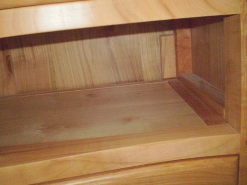 Finition du logement d'un tiroir de la commode galbée en chêne massif, modèle XVIII°. Détail.