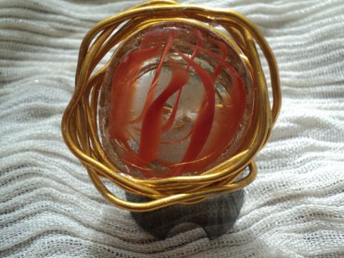 Bague en fil d'aluminium et galet en verre,parsemé de fil orange. La bague s'adapte à toutes les tailles de doigt