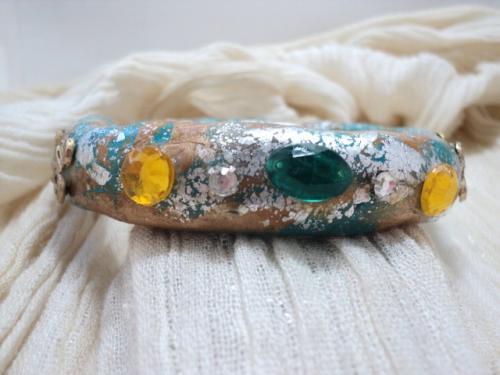 Bracelet en pâte fimo bleue et caramel,travaillée avec des feuilles d'argent et verni.Le bracelet est décoré de strass verts et jaunes et d'estampes dorées.  Ce bracelet convient aux petits poignets ou aux adolescentes.