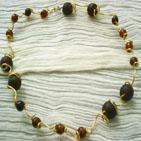 NEGRESCO: Tour de cou en fil d'aluminium doré tordu et entourant des perles de verre de couleur ambre et de verre mat marron