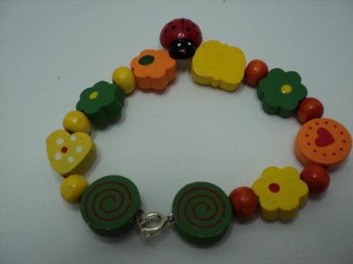 COCCINELLE:Bracelet sur fil câblé flexible. Les perles sont en bois de formes différentes et amusantes et couleurs variées. le milieu de bracelet est décoré avec une coccinelle en bois.Le bracelet se ferme avec un fermoir mousqueton en métal argenté.