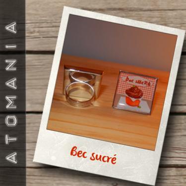 Bague « Bec sucré » - ATOMANIA composée d?une image créée par « Atomania », protégée par résine transparente, montage sur support de bague bronze carré réglable. Format : 25 x 25 mm. Expédition sous huitaine après réception du paiement.