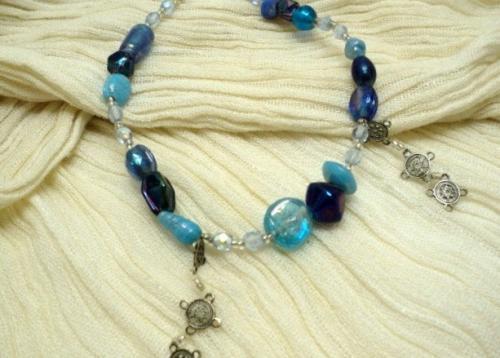 AGADIR:Bracelet en perles de verre et porcelaine de formes diff�rentes et de bleu diff�rents. Elles sont s�par�es trois par trois par des facettes bleu