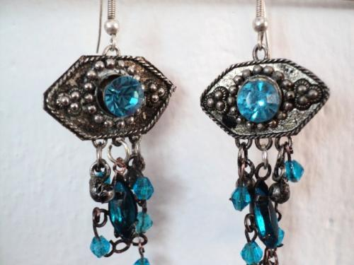 Boucle d'oreille composées d'une estampe en fer argenté décorée d'un strass bleu Les pendants sont composés de perles en verre bleu et grelots en métal