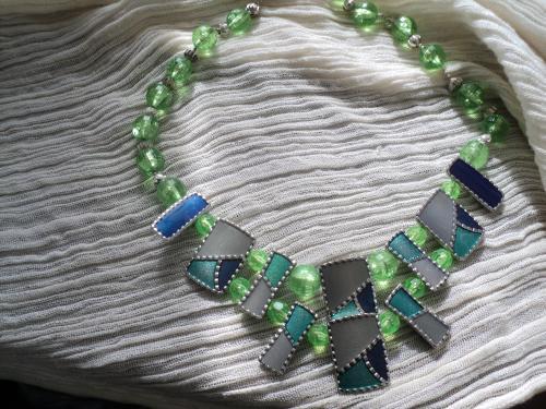 Collier composé de plaques de métal argenté peintes soit en vert,émeraude,gris Chaque plaque est séparée de la suivante par des perles en plastique vert et constitue le tour du cou avec des perles rondes en métal argenté