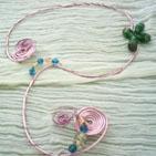 SPRING: Collier en fil d'aluminium rose en forme de s inversé chaque branche se termine par un tortillon. Au milieu une étoile verte composée de perles cloisonnées,et des perles en verre bleu et blanc le décore à plusieurs endroits.