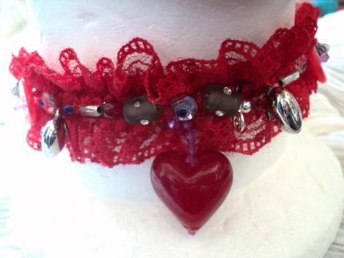 Tour de cou en dentelle rouge froncé décoré  de perles de toute formes et tailles en rouge et mauve.Un coeur rouge en verre pend au milieu du tour de cou.Petits strass rouges et mauves sont éparpillés un peu partout de la dentelle fermeture par une scratch