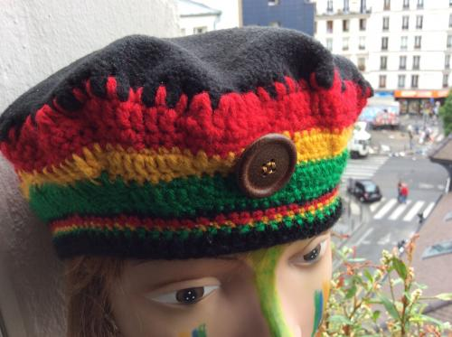 Un bien joli bonnet tricot� laine aux couleurs vives de la  Jamaique. Un bouton en bois orne le tout. Le top est fait de polaire noire d'o� une plus grande l�gert�. Mod�le unique . Tour de t�te : 60