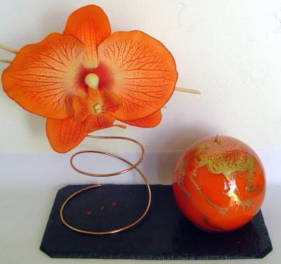 Porte Bougie Orchidée Orange  Dimensions du socle : 16cm de long. 9cm de large.  L'ardoise est vernie.  La bougie est en cire végétale et recouverte d'un vernis. Son diamètre est de 6 cm. (d'autres coloris de bougie sont disponibles sur simple demande)