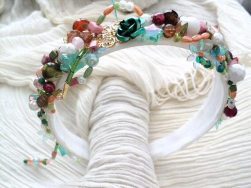 MARIE-ANTOINETTE:Serre-t�te en plastique blanc recouvert � l'int�rieur comme � l'ext�rieur d'un tissus blanc.Le serre-t�te est recouvert d'une multitude de perles diff�rentes et de couleurs diff�rentes: estampe dor�e, fleurs en m�tal vert, �toiles en verre, fleurs en plastique brillant, coeur en cristal de swaroski, rocailles, perles de culture, tubes en verre, facettes, toupies, perles rondes en verre, en porcelaine et en plastique... Un fil de perles pend d'un c�t� du serre t�te.