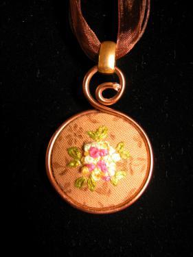 Collier avec médaillon brodé dans un camaieu de roses et jaune sur fond noisette, lacet en coton ciré et organza. Diam 30mm