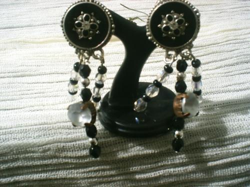 ETOILE FILANTE Boucles d'oreille sur clips, support en métal, fleur argentée sur fond noir surmontée d'un petit strass. Pendants divisés en trois branches de facettes en cristal de swaroski noir et transparent, rocailles noires et perles argentées. Une des branches porte un cabochon blanc opaque. Longueur 5 cm.