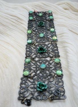 CHARLOTTE! Bracelet composé de  cinq estampes argentées, décorées avec des fleurs en métal vert et des perles plates en verre vert.Le bracelet se ferme avec deux clips
