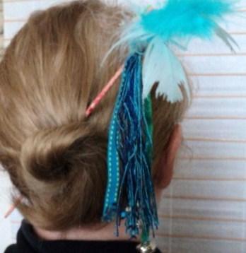 CORDELETTE:Pic à cheveux sur tige en bois peint et verni, agrémenté de plumes bleues, décorées d'étoile en mousse multicolore, chaque pendantde coton ou fil de soie, est orné soit de perles, de coeur.