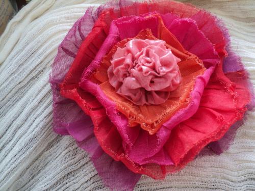 Broche en tissu et p�te fimo.Une rose d�core plusieurs rangs de tissu orange,rose,rouge,et mauve. Epingle s�curis�e en m�tal argent� au dos