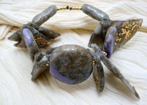 PURPLE:Bracelet,composé de perles en pâte fimo.La pâte fimo grise a été agrémentée de morceaux de feuilles d'or qui se présentent soit en triangle soit en perles allongées, les perles rondes sont mélangées avec de la pâte fimo violine et le tout verni. Les perles sont séparées par de petites perles dorées. Le tout est monté sur un fil d'aluminium argenté et donne la possibilité d'adapter le bracelet à tous les poignets