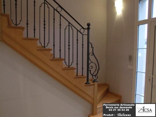 Rampe d'escalier en fer forgé avec une main courante en acier mouluré et départ forgé.