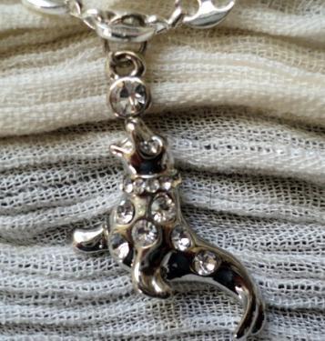 PINGUOIN:Pendentif en métal argenté recouvert de stass transparents de tailles différentes selon l'emplacement sur le corps ou sur le collier. Le ballon est un gros strass transparent. Ce pendentif convient à une adolescente ou même à une femme. Il brille de mille feux