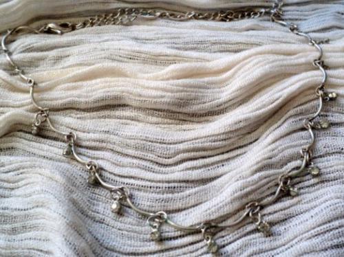 ADELINE: Collier réglable, constitué d'une enfilade de demi-cercles en métal argenté, séparés par des petits strass transparents.Ce collier est ajustable grâce à une chainette que vous pouvez réglér à la hauteur désirée.