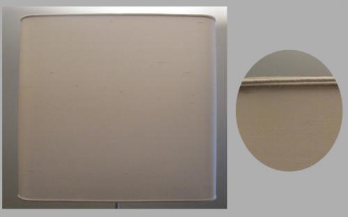 Abat-jour rectangulaire réalisé en soie avec une finition simple ton sur ton.   Sur un pied de lampe en verre, l'ensemble donne un style très épuré.