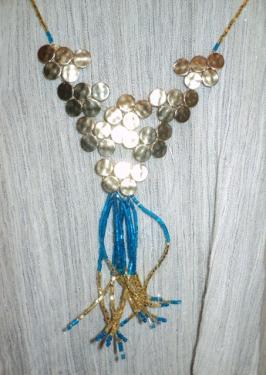 Collier mi-long en perles de rocailles bleues et or et estampes dorées. Le collier est fabrique avec du fil de nylon.