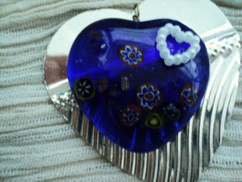 Pendentif en verre de murano en forme de coeur accroché sur un coeur en métal argenté.Un petit coeur en plastique décore le coeur en verre de murano.