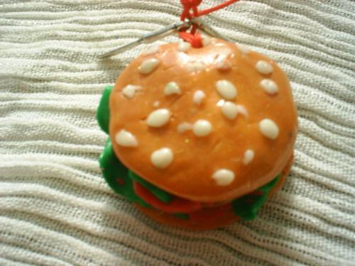 MIAM-MIAM: collier sur fil de coton cir� rouge, pendentif en p�te fimo verni en forme de hamburger, 2 petites breloques en forme de couteau. Longueur ajustable.