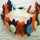 BOUTONS FLEURIS: Collier en feutrine compos� de fleurs orange et bleu marine.Les fleurs ont en leur centre des boutons de couleurs diff�rentes.Fermoir mousqueton dor�.