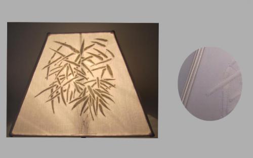 Abat-jour Pyramidal confectionné à partir d'un boutis réalisé par la cliente. Pour mettre en valeur ce joli travail, j'ai souligné le tout avec une double soutache.