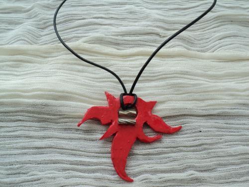 Satan: Pendentif pour homme en pâte fimo rouge. Décoré par une perle allongée et striée en métal argenté. Le lien est en cuir noir.Ce pendentif s'adapte à toute les tailles de cou.
