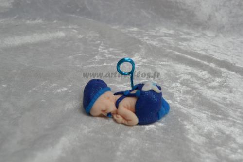Bébé petit lutin bleu. Produit fait main. Bébé en pâte polymère (fimo). Bonnet et pantalon bleu pailleté, chaussette bleu, tétine bleue. L 3 cm / l 6.5 cm / H 3 cm Tige porte photo en aluminium bleu. Pays d'expédition : France. + frais de port 3,00 euros (ref bb47)