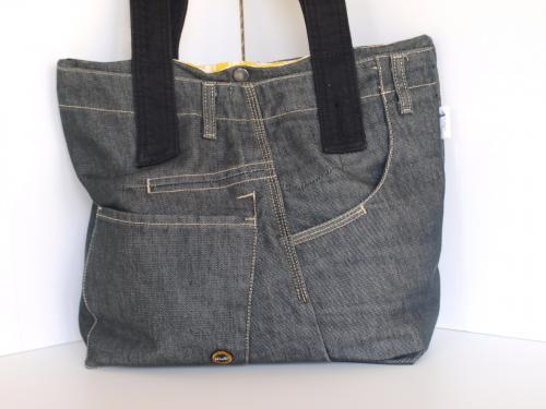 sac à main en patchwork de jean noir, porté épaule Matériaux utilisés: Coton, Jean  ce sac a été crée à partir d'un jean noir homme  il possède trois poches extérieures récupérées sur le jean  il est doublé avec un tissu rayure jaune, style toile à matelas doté d'une poche intérieure:14x11cm  il se porte à l'épaule avec deux anses noires de 75cm  il se ferme avec un bouton pression métallique  ses dimensions:hauteur:31cm, largeur bas:29cm, profondeur 11.5cm  un morceau de cuir doublé amovible pour le fond du sac(29x11.5)permet une certaine rigidité  il est lessivable en machine à 30°C