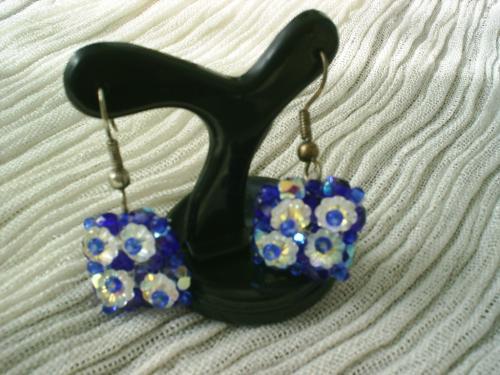DOMINO:Boucles d'oreille pour oreilles percées sur crochet argenté. Carré de petites facettes bleu irisé et rocaille bleue,surmonte de quatre fleurs de couleur blanche irisée, au coeur de rocaille bleue. Longueur: 3cm